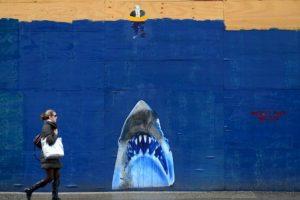 Una mujer pasa frente a la imagen de un tiburón en Estados Unidos. Foto:AFP. Imagen Por: