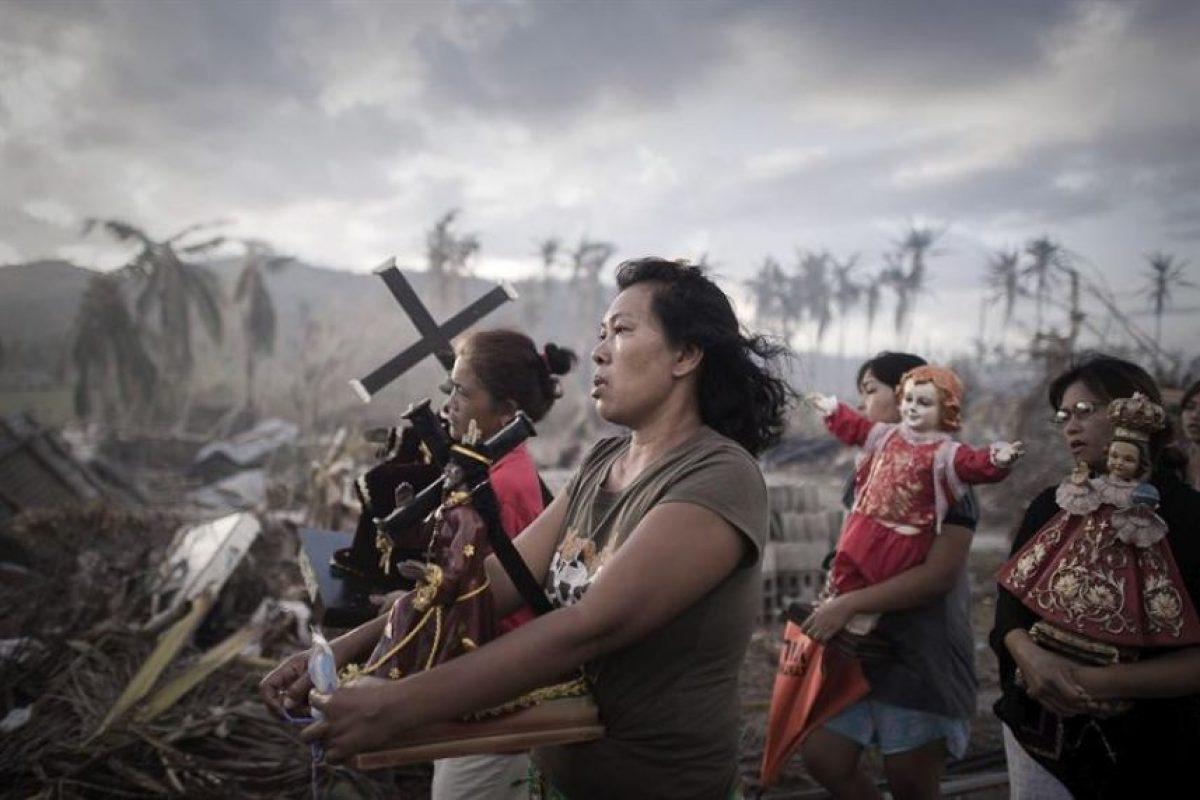Fotografía realizada por el francés Phillipe Lopez, de la Agencia France Presse (AFP), que ha ganado el primer premio en la categoría de Noticias de Actualidad de la 57ª edición del World Press Photo. Esta fotografía muestra a los supervivientes del tifón Haiyán, que afectó el centro de Filipinas en noviembre de 2013 y causó más de 6.200 muertos, en una procesión religiosa en Tolosa, en la isla de Leyte. Foto:EFE. Imagen Por: