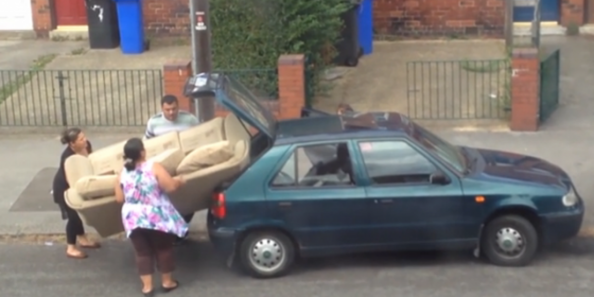Familia intenta meter un enorme sofá en un pequeño auto