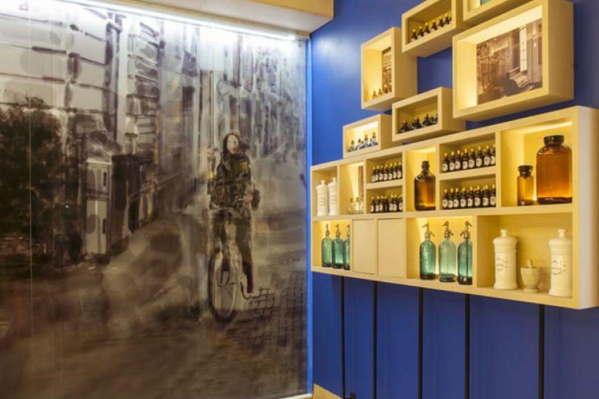 """Bernardita Verdugo – """"La Botica de Marisa"""". Concepto actualizado en diseño y tecnología de la antigua botica, una mezcla entre el pasado y el futuro de la farmacia. Al centro se emplaza el lugar del químico que crea los medicamentos, lo que a su vez interactúa con un muro repleto de cajitas desfragmentadas, representando el paso del tiempo desde 1940 a 2014. Los materiales predominantes son cristales de color blanco con un toque verdoso, madera natural, porcelanato y acero,además del azul que refleja un concepto tecnológico y moderno. Foto:CasaCor. Imagen Por:"""