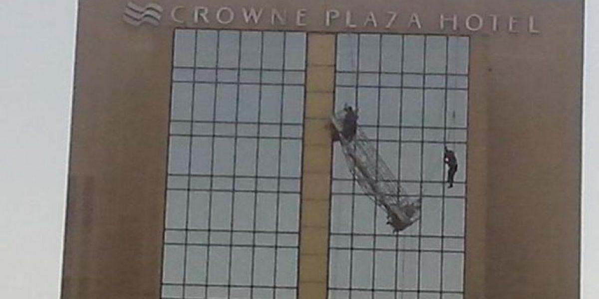Impactante: Trabajadores cuelgan de un andamio desde gran altura en el Hotel Crowne Plaza