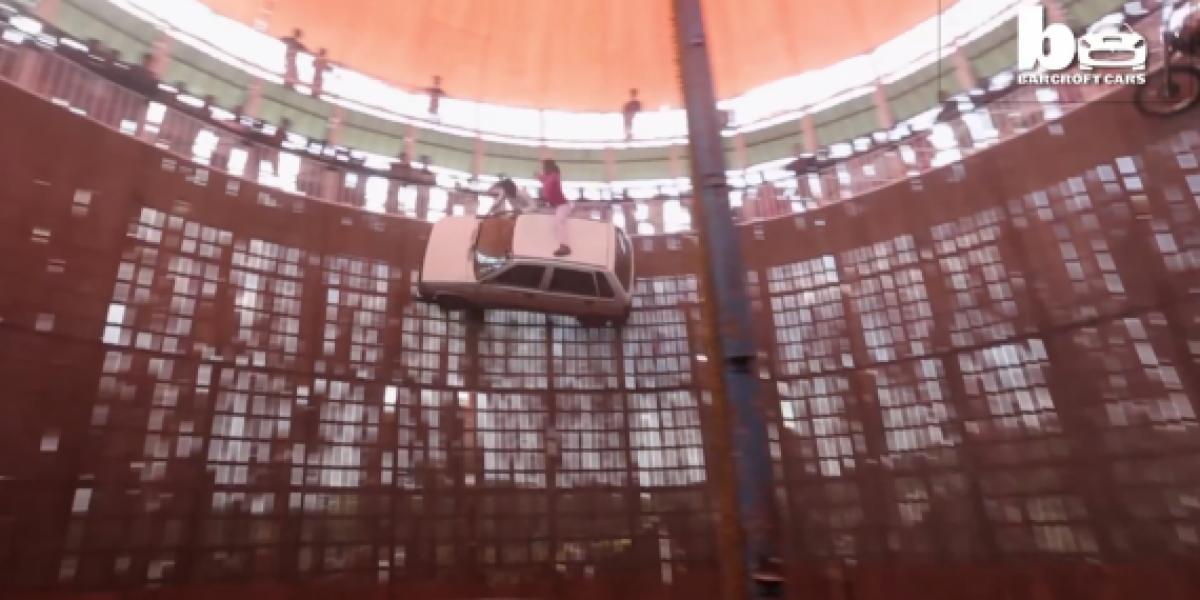 Motocicletas y autos con personas en el techo se pasean por el muro de la muerte