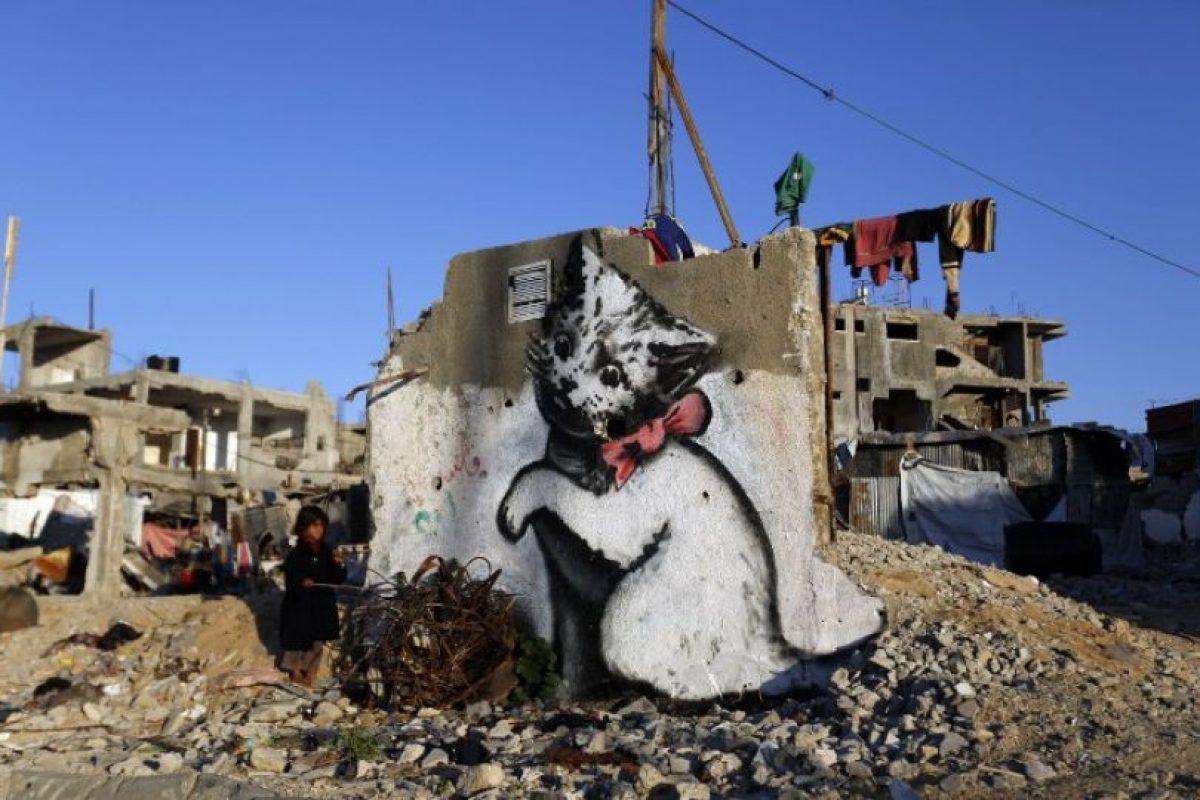 Un niño se para junto a un mural pintado por el artista británico Banksy, en las ruinas de la Franja de Gaza Foto:AFP. Imagen Por: