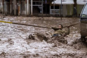 Un hombre se aferra a una línea de seguridad para cruzar una calle inundada por el desbordamiento del río Copiapó debido a las fuertes lluvias que afectaron a algunas zonas de la ciudad,en Copiapó, Chile el 26 de marzo de 2015. Foto:AFP. Imagen Por: