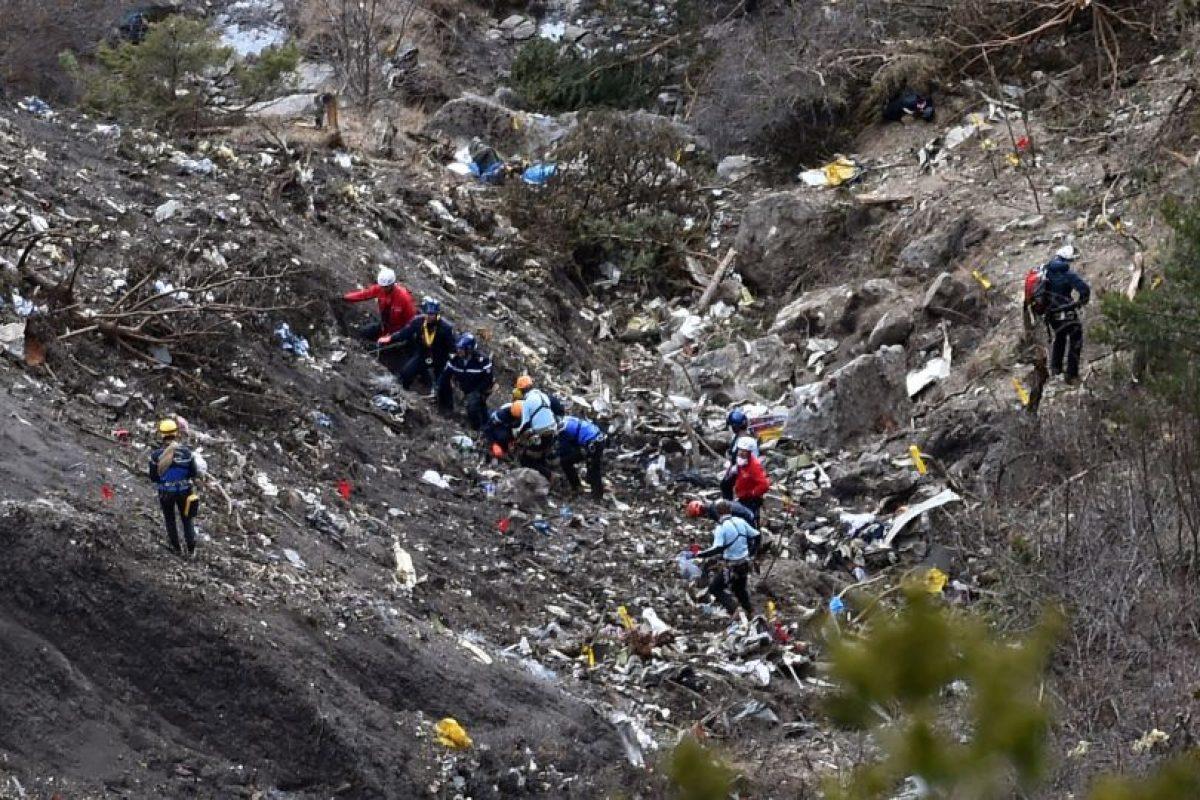 Investigators trabajan cerca de la zona de los de escombros diseminados mientras hace su camino a través del sitio del accidente del A320 Germanwings Airbus. Foto:AFP. Imagen Por: