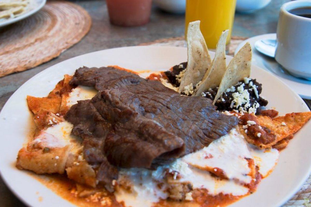 Una comida mexicana de tortilla frita sumergida en salsa o mole, tradicionalmente acompañados con queso y otros acompañantes (como cebolla, pollo o huevos revueltos) Foto:Wikimedia.org. Imagen Por:
