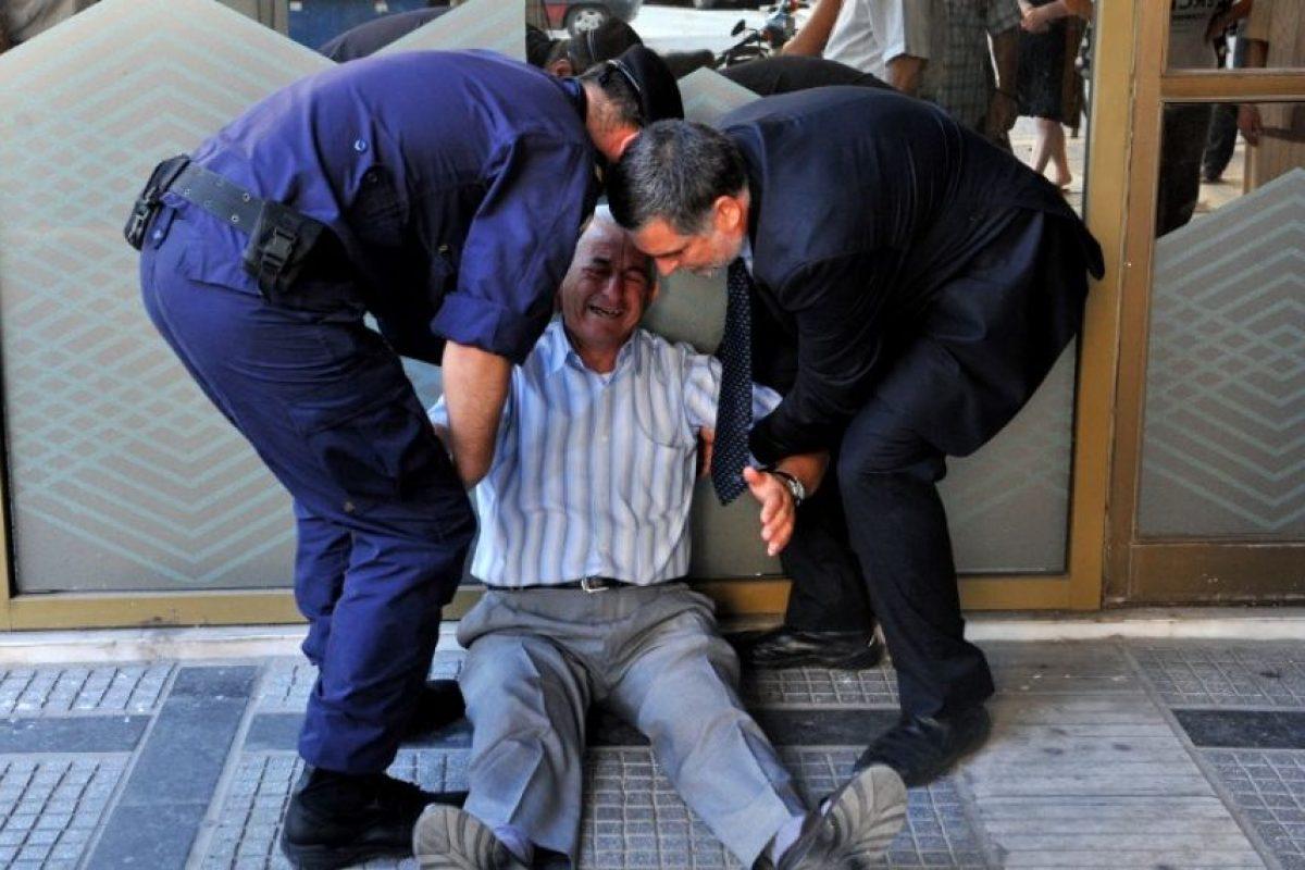 Un pensionado llora afuera de un banco Foto:AFP. Imagen Por: