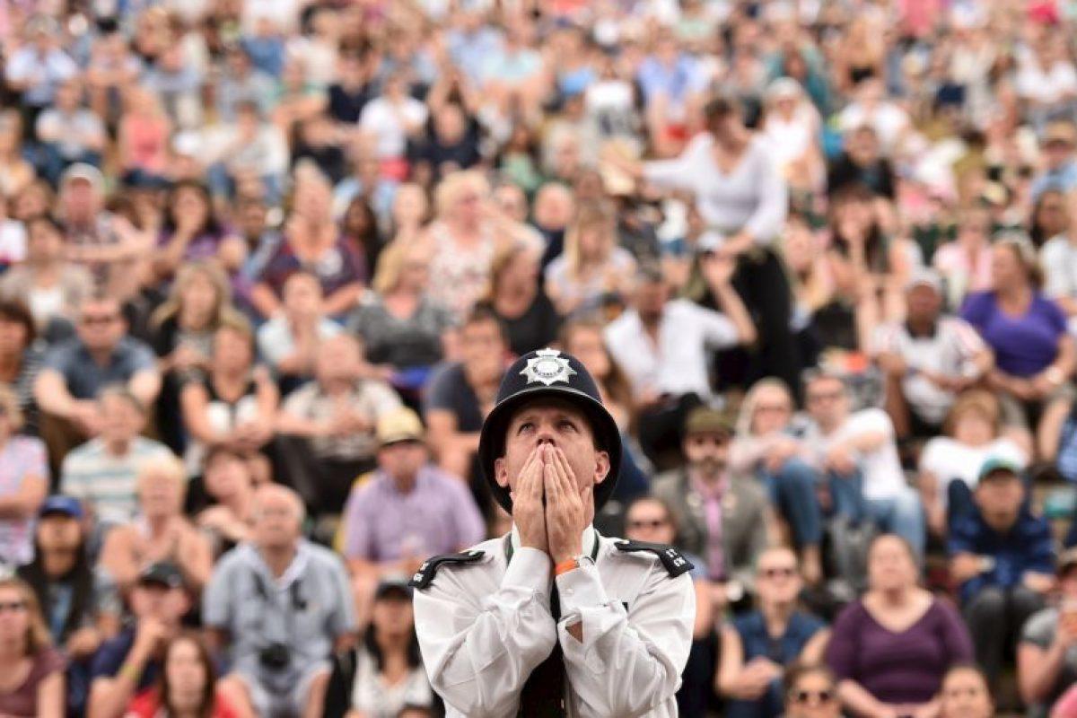 Un oficial de policía británico reacciona cuando ve una pantalla gigante que muestra el Campeonato de Wimbledon. Foto:AFP. Imagen Por: