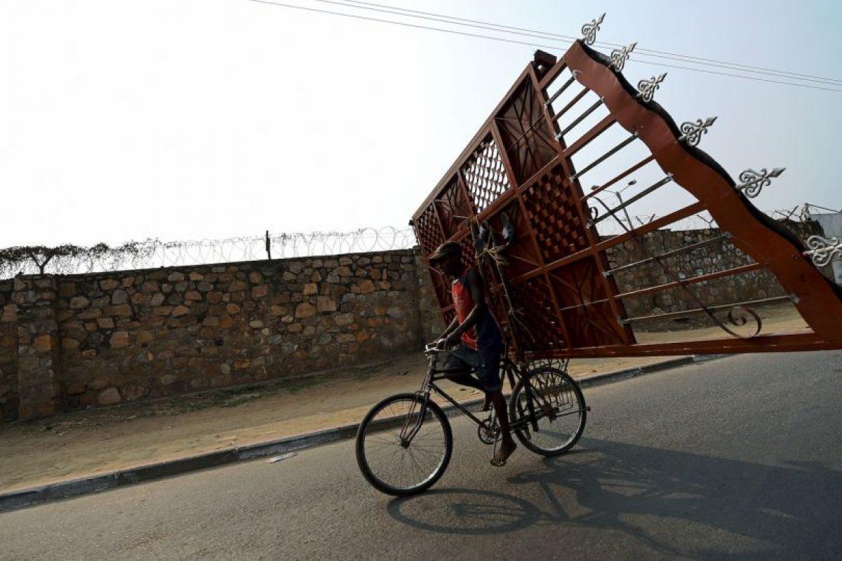 Hombre carga una puerta de metal en su bicicleta en Burundi. Foto:AFP. Imagen Por: