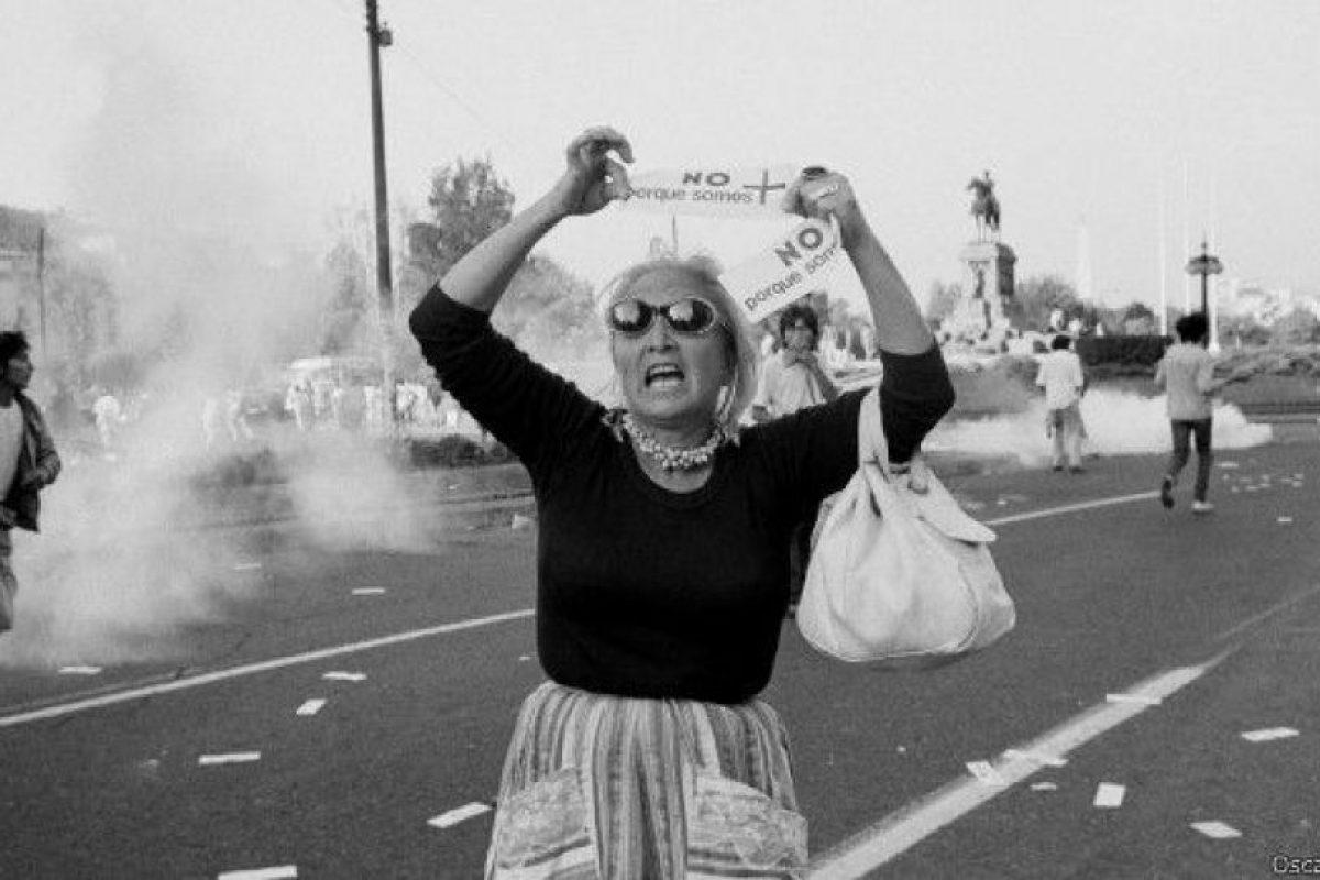 Las imágenes en blanco y negro muestran instantes de tenso dramatismo, retratos de las figuras emblemáticas, noches de toque de queda y cotidianas jornadas de protesta y represión policial, como la de esta foto capturada por Óscar Navarro durante el Día de la Mujer en 1986. Foto:Óscar Navarro. Imagen Por: