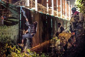 Migrante brinca valla de seguridad en Francia. Foto:AFP. Imagen Por: