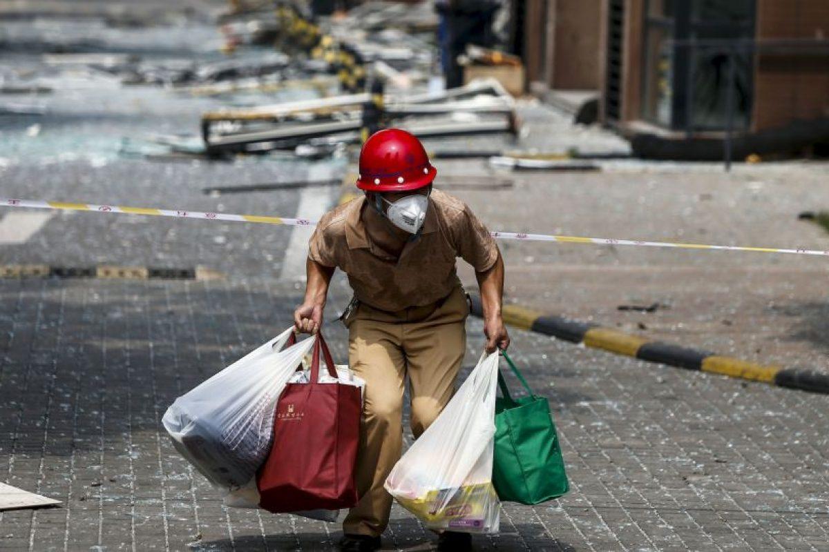 Víctima de las explosiones en China carga sus pertenencias en busca de un lugar seguro. Foto:AFP. Imagen Por: