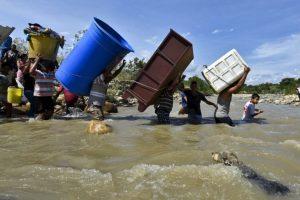 Colombianos deportados cargan sus pertenencias por el río Táchira. Foto:AFP. Imagen Por: