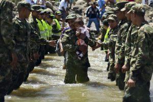 Bebé es cargado en el Río Táchira, entre la frontera de Venezuela y Colombia. Foto:AFP. Imagen Por: