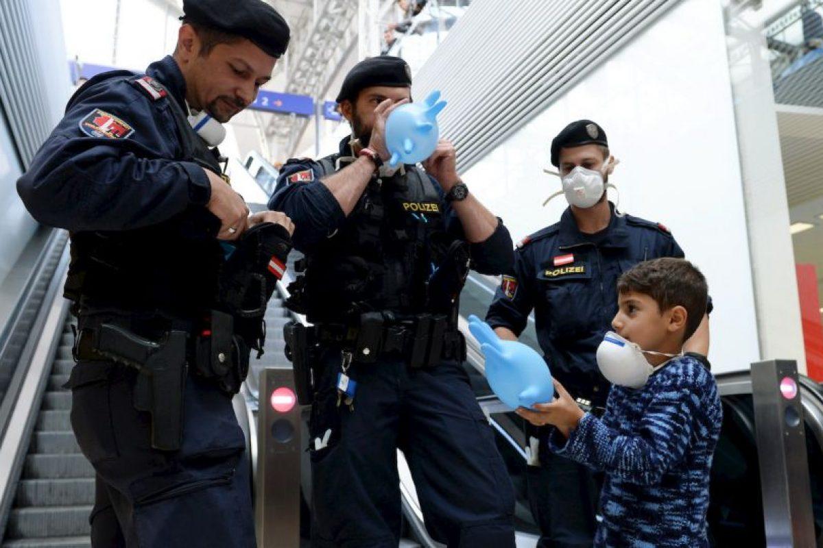 Policías australianos llenan guantes como si fueran globos para que un refugiado sirio juegue. Foto:AFP. Imagen Por: