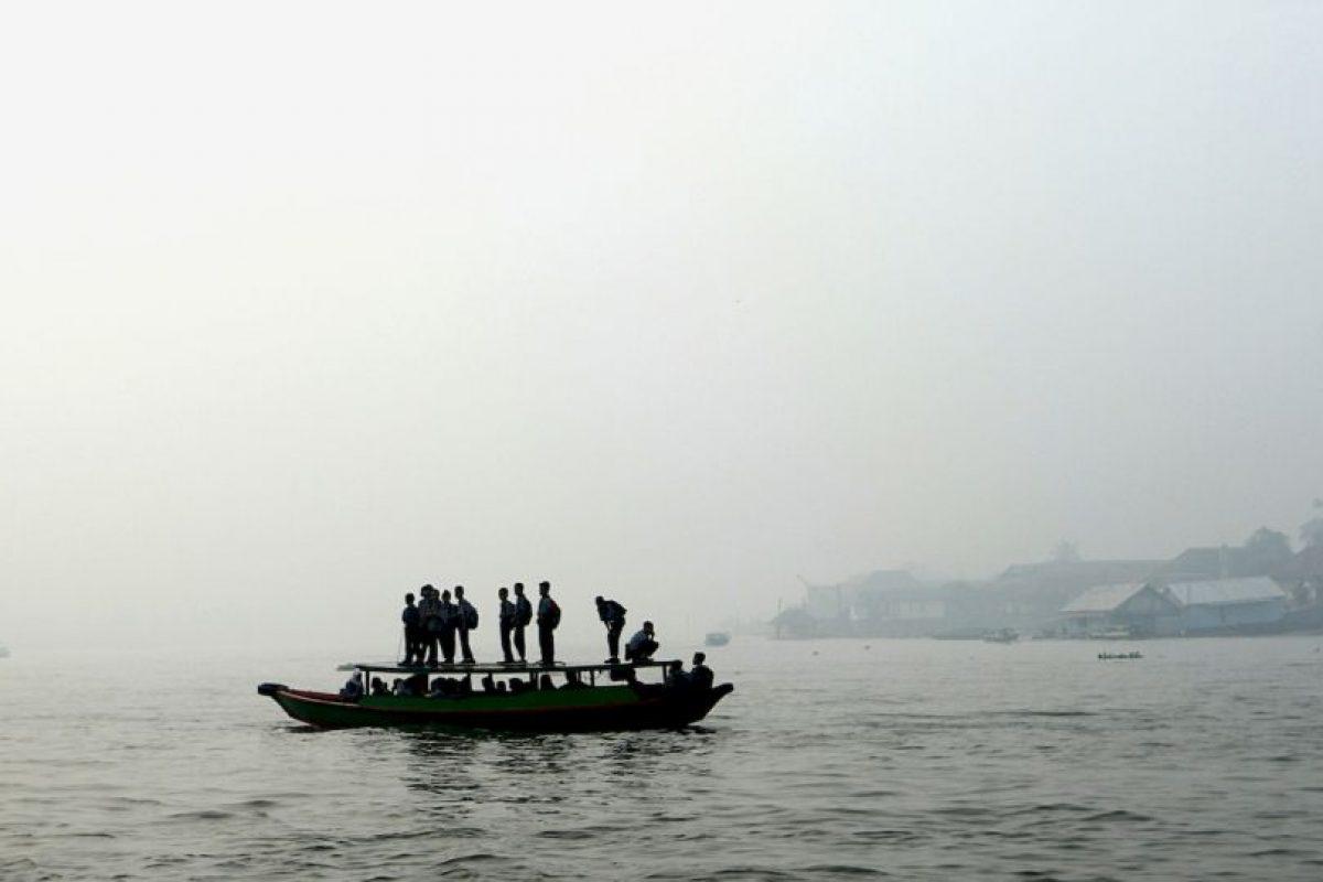 Estudiantes indonesios verifican fuego forestal desde un barco. Foto:AFP. Imagen Por: