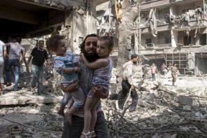 Hombre trata de salvar a dos niñas tras detonaciones de bomba en Siria. Foto:AFP. Imagen Por: