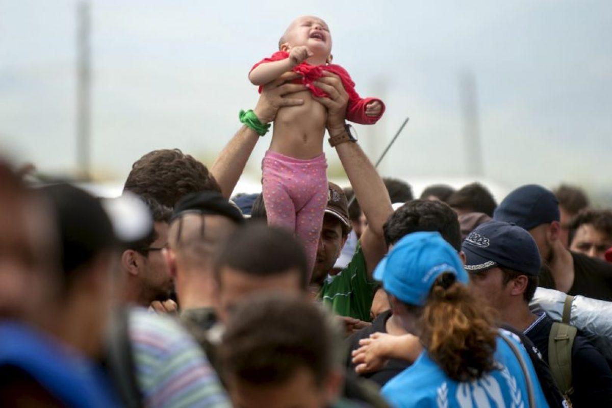 Hombre carga a una bebé entre los refugiados y migrantes en la frontera de Grecia y Macedonia. Foto:AFP. Imagen Por: