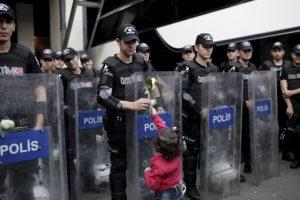 Niña migrante le regala una flor a un policía antidisturbios turco. Foto:AFP. Imagen Por: