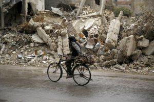 Hombre pasa en su bicicleta por una zona destruida por el conflicto en Siria. Foto:AFP. Imagen Por: