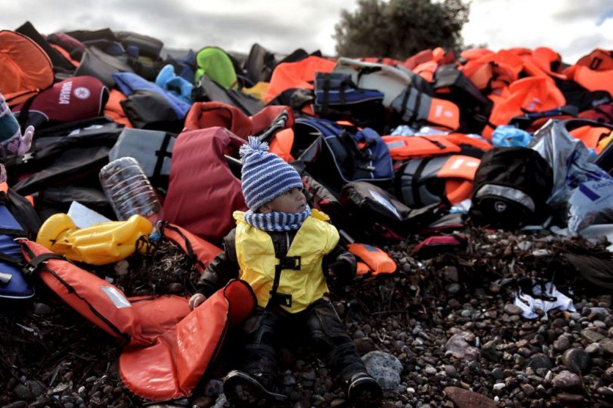Niño refugiado sentado sobre una pila de chalecos salvavidas en la isla Lesbos. Foto:AFP. Imagen Por: