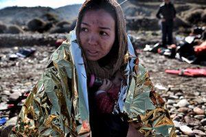 Refugiada protege a su hijo en una manta termanl a su llegada a Lesbos. Foto:AFP. Imagen Por: