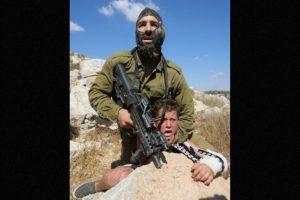 Muestran a un soldado ejerciendo presión sobre un menor de edad, quien presuntamente le arrojó piedras Foto:AFP. Imagen Por: