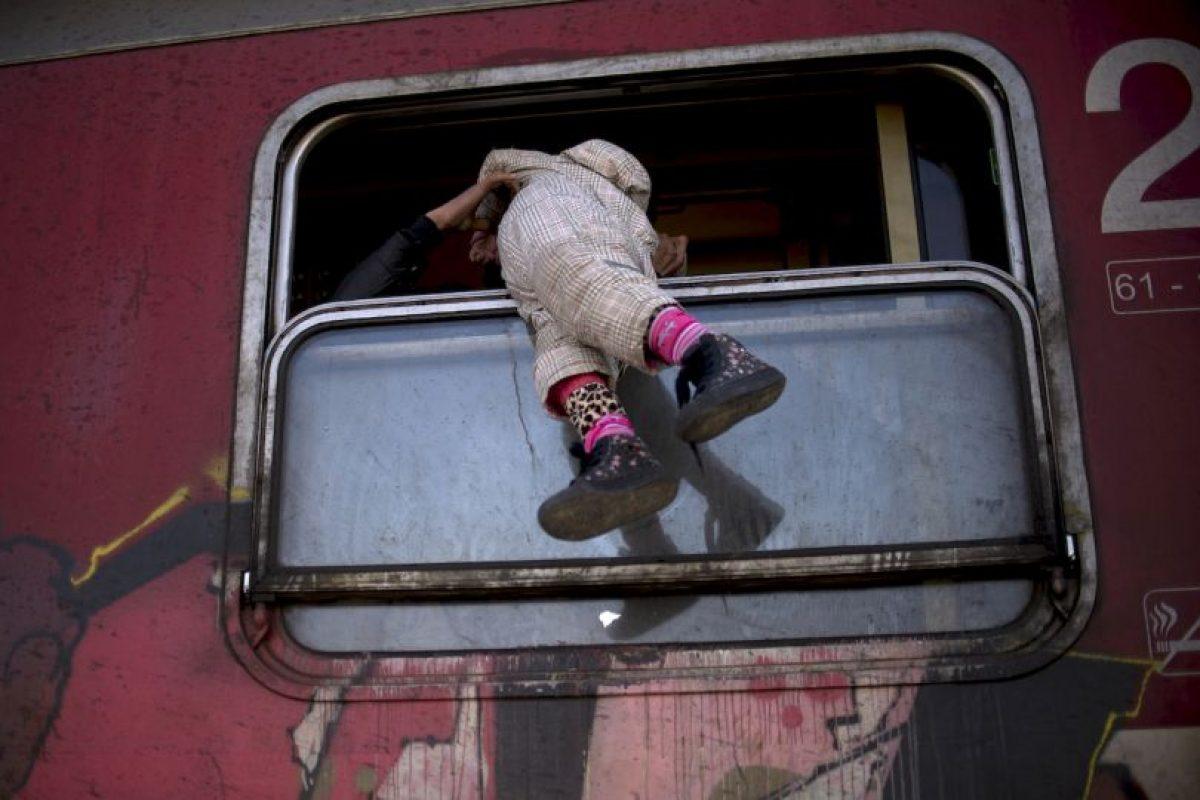 Migrante carga a niña por la ventana del tren camino a Serbia. Foto:AFP. Imagen Por: