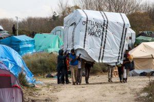 Migrantes mueven una tienda en Calais, Francia. Foto:AFP. Imagen Por: