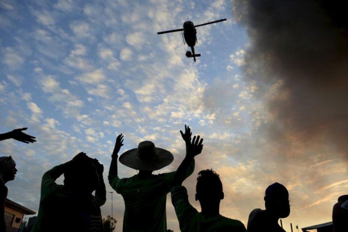 Residentes hacen señas a un helicóptero para que ayude a apagar incendio en Manila, Filipinas. Foto:AFP. Imagen Por: