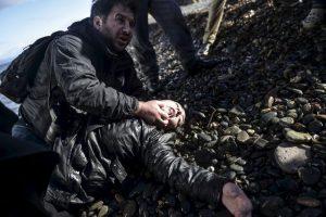 El fotógrafo Giorgos Moutafis ayuda a una migrante herida en la isla de Lesbos. Foto:AFP. Imagen Por: