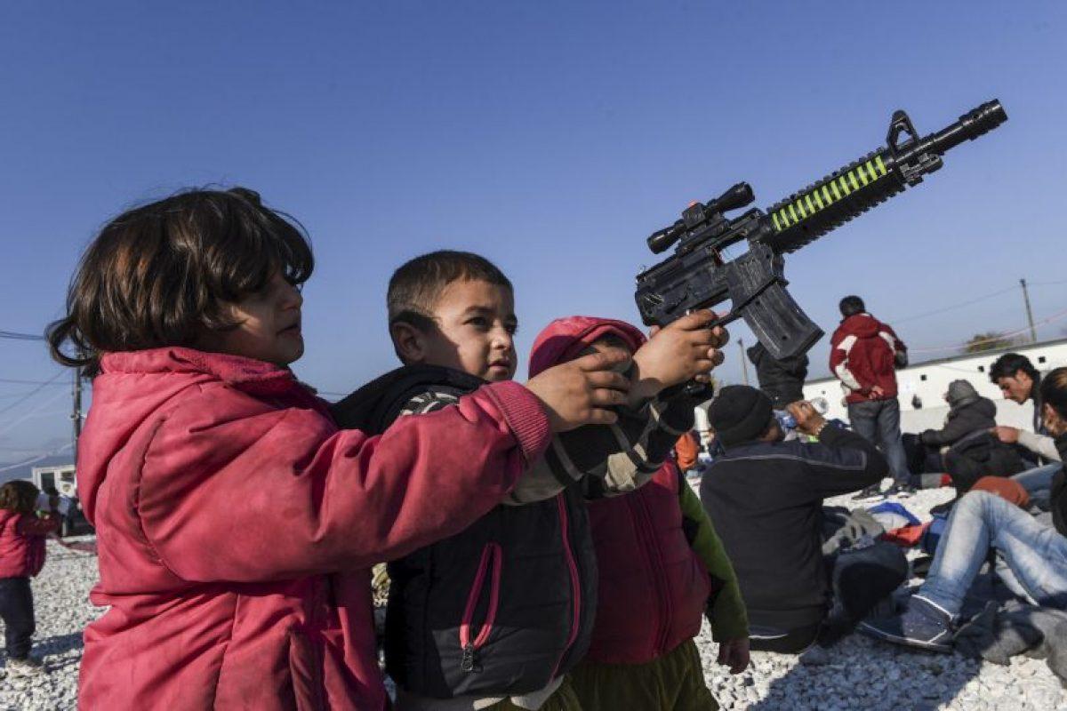 Niños juegan con un arma de mentira en la frontera de Grecia y Macedonia. Foto:AFP. Imagen Por: