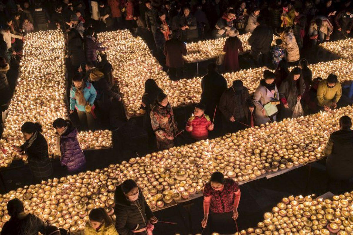 La gente enciende lámparas durante el Festival de la lámpara de la mantequilla en China. Foto:AFP. Imagen Por: