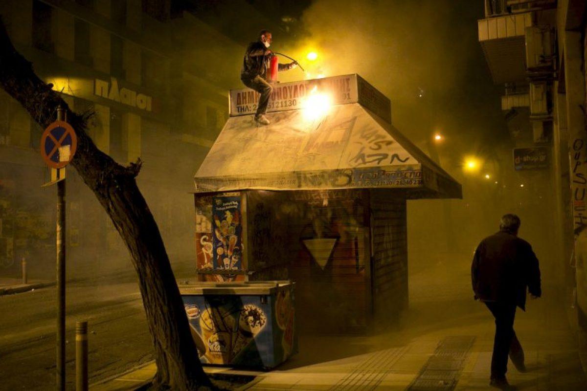 Un vendedor trata de apagar un incendio en su kiosco durante los enfrentamientos entre la policía antidisturbios y manifestantes en Atenas. Foto:AFP. Imagen Por: