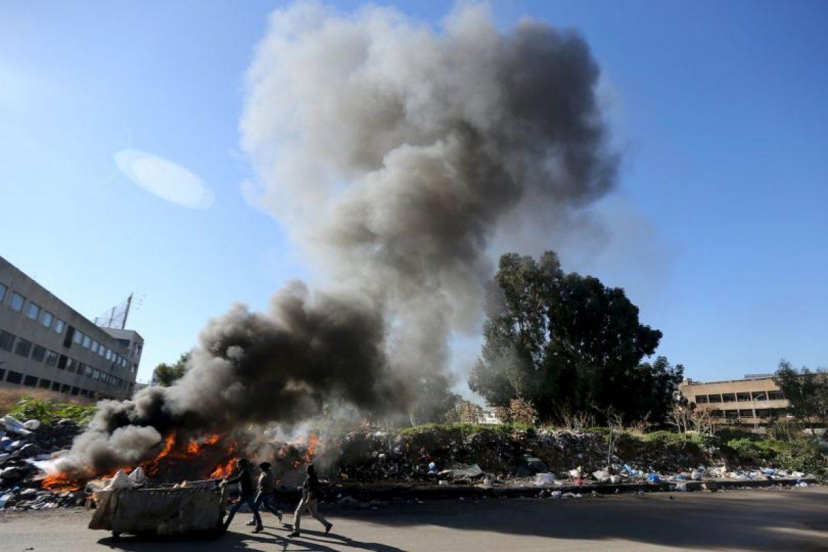 Recicladores de basura empujan su carrito frente a la quema de una pila de desechos en Beirut, Líbano. Foto:AFP. Imagen Por: