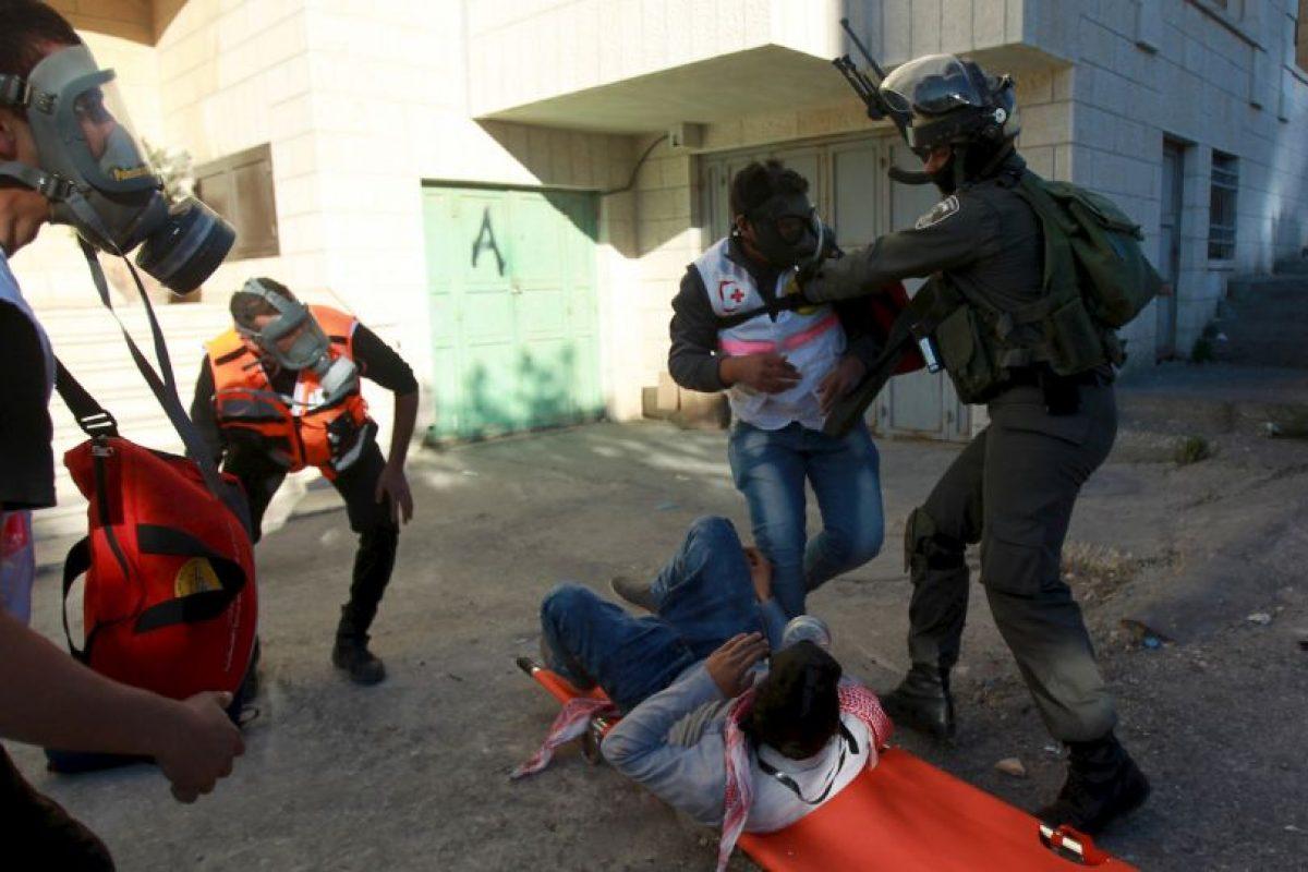 Un paramédico palestino intenta evitar que un guardia fronterizo israelí detenga al manifestante tendido en la camilla. Foto:AFP. Imagen Por: