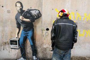 Steve Jobs como el hijo de un migrante de Siria. Foto:vía banksy.co.uk. Imagen Por: