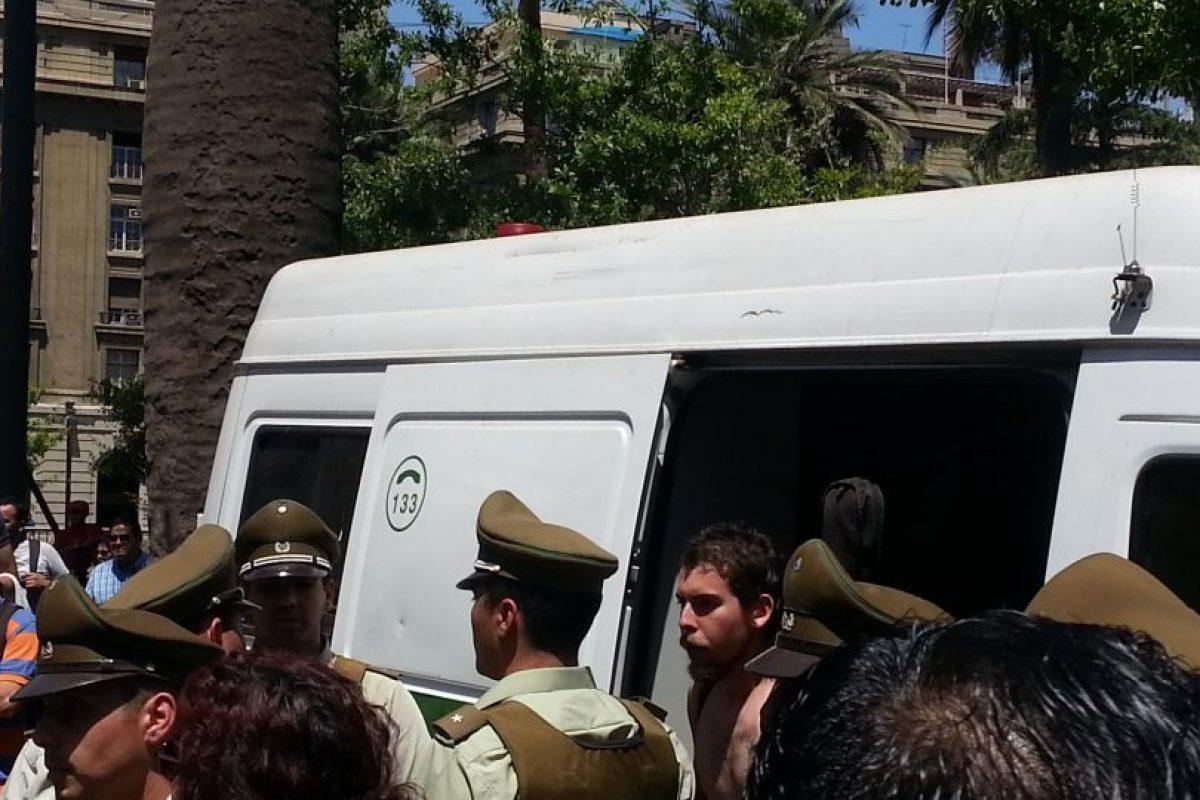 El joven siendo trasladado hasta otro carro policial para ser llevado a la 1ª Comisaría de Santiago. Foto:Publimetro / Víctor Jaque. Imagen Por:
