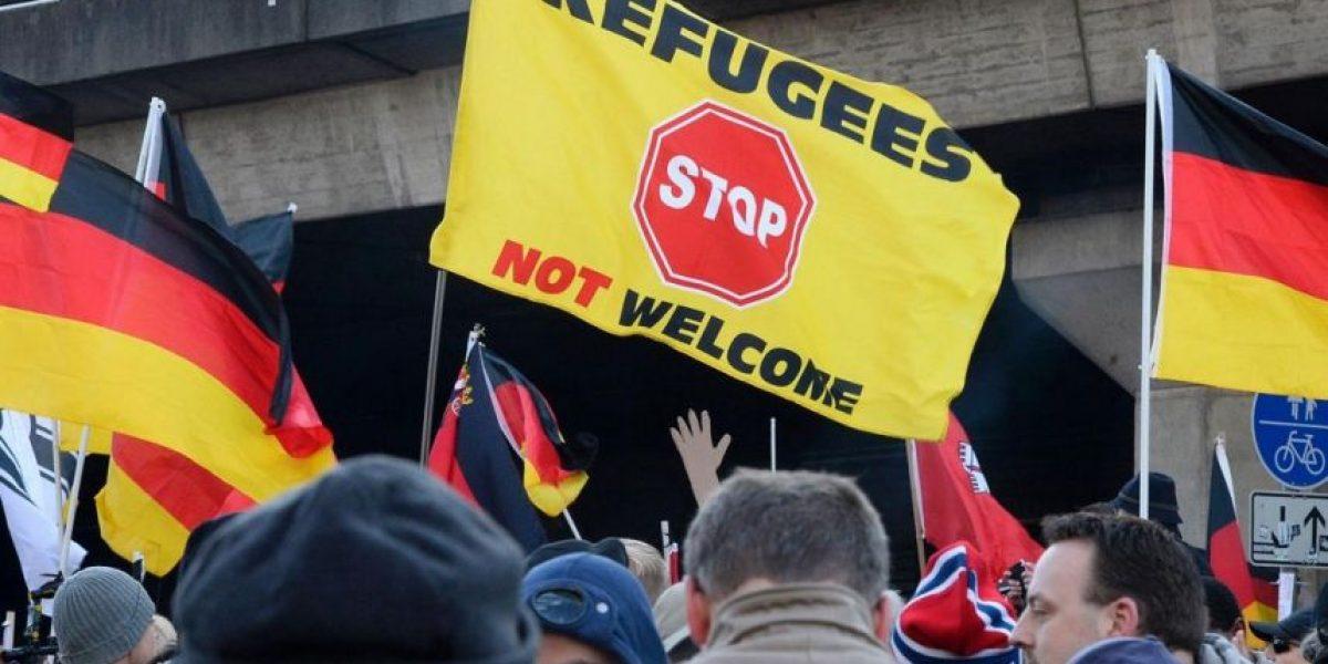 Un alemán con bigote de Hitler y casco nazi ataca a varios refugiados