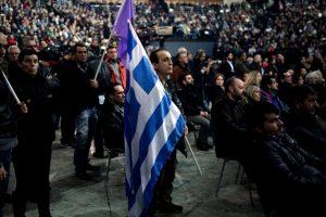 Un hombre sostiene una bandera griega durante el discurso de Alexis Tsipras de este domingo, con motivo del primer año de su gobierno. Foto:AFP. Imagen Por: