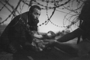 Foto del año. Tomada por Warren Richardson. Muestra a un hombre pasando a un bebé por una valla en construcción entre Serbia y Hungría Foto:worldpressphoto.org. Imagen Por: