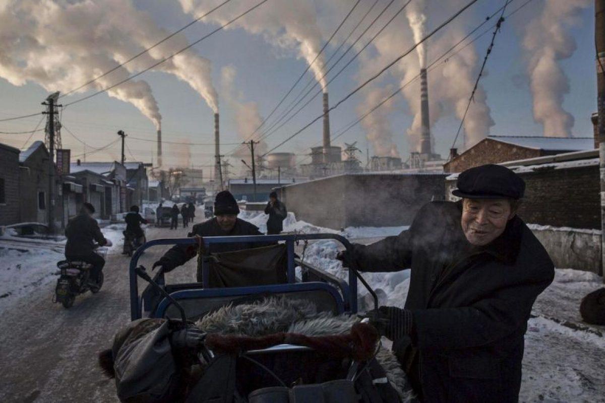 Kevin Frayer. Un anciano chino empuja un triciclo junto a un fábrica en China Foto:worldpressphoto.org. Imagen Por: