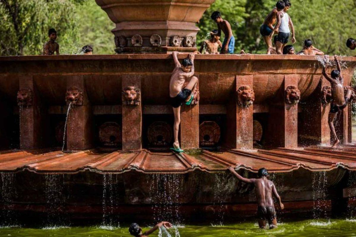 Los pequeños de la India aprovechan cualquier fuente para refrescarse y huir de la masa de aire caliente Foto:Getty Images. Imagen Por: