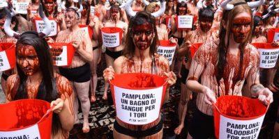 Un centenar de activistas se desnudan y se tiñen de rojo contra los encierros en San Fermín