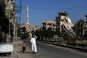 Un hombre y su hijo caminan por un suburbio destruido de Damasco, la capital de Siria. Foto:AFP. Imagen Por: