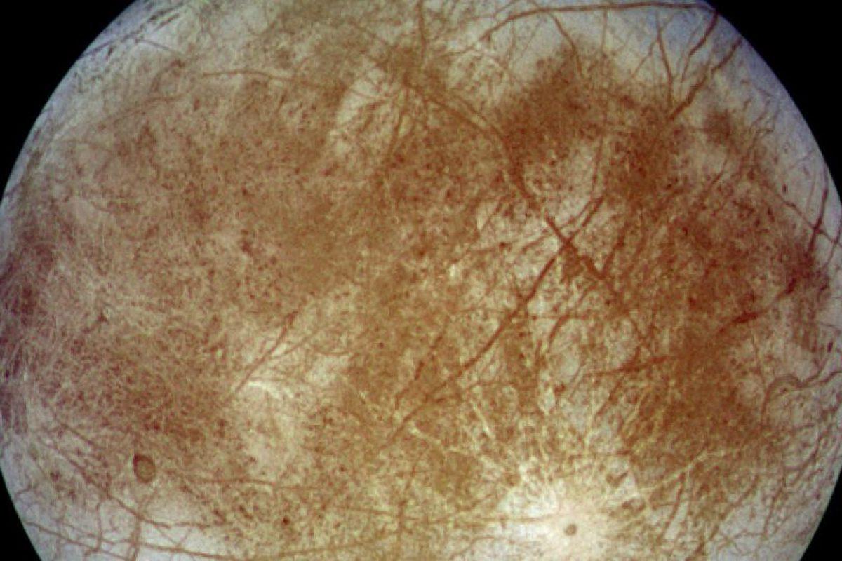 Europa, luna de Júpiter. Los científicos sospechan fuertemente que un océano salado bajo la superficie se encuentra debajo de la corteza helada de Europa. El calentamiento por marea de su planeta madre, Júpiter, mantiene el estado líquido de este océano, y también crea bolsillos parcialmente derretidos, o lagos, a lo largo de la cáscara externa de la luna.. Imagen Por: