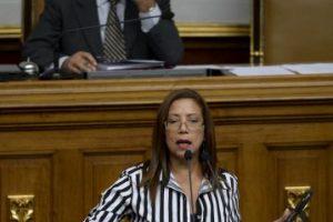 Diputada chavista muestra un retrato de Hugo Chávez, mientras que el presidente de la Asamblea Nacional, el opositor Henry Ramos Allup, se cubre el rostro Foto:AFP. Imagen Por: