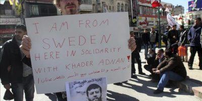 Un ciudadano sueco sujeta un cartel en apoyo al preso palestino Jader Adnan, detenido sin cargos desde diciembre pasado por el Ejército israelí, durante una manifiestación para pedir su puesta en libertad, en Naplusa (Cisjordania), el 21 de febrero de 2012. Jader Adnan decidió hoy abandonar su huelga de hambre tras 66 días sin comer en protesta por su arresto sin acusación y por supuestos malos tratos por parte de soldados israelíes. EFE