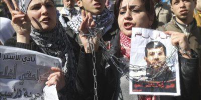 Palestinos gritan consignas en favor del preso palestino Jader Adnan (en la foto), detenido sin cargos desde diciembre pasado por el Ejército israelí, durante una manifiestación para pedir su puesta en libertad, en Naplusa (Cisjordania), el 21 de febrero de 2012. Jader Adnan decidió hoy abandonar su huelga de hambre tras 66 días sin comer en protesta por su arresto sin acusación y por supuestos malos tratos por parte de soldados israelíes. EFE