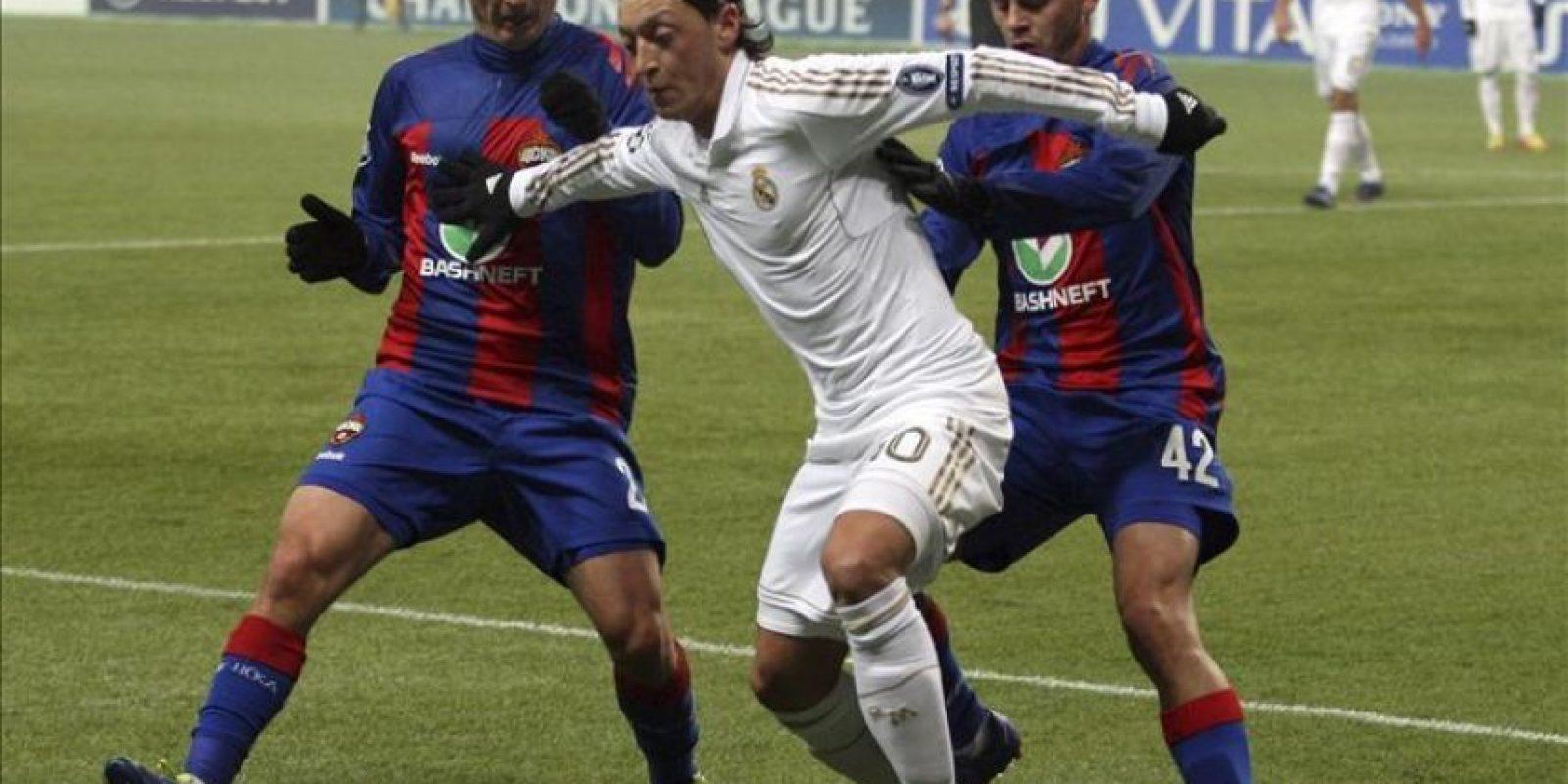 El centrocampista alemán del Real Madrid Mesut Özil (c) controla el balón ante Evgeni Aldonin (i) y Georgi Schennikov (d), del CSKA Moscú, durante el partido de ida de octavos de final de la Liga de Campeones que sus equipos disputaron en Moscú, Rusia. EFE